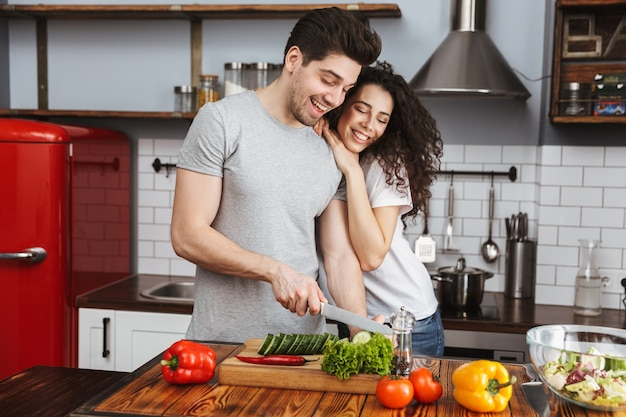 Beau couple homme et femme cuisinant salat avec des légumes ensemble dans une cuisine moderne à la maison