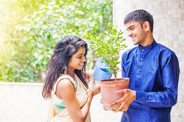 Beau couple indien arrosant la plante dans le jardin sur leur balcon à la maison