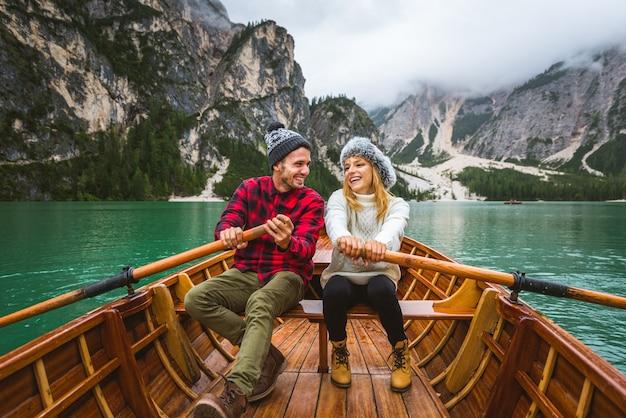 Beau couple de jeunes adultes visitant un lac alpin à braies italie