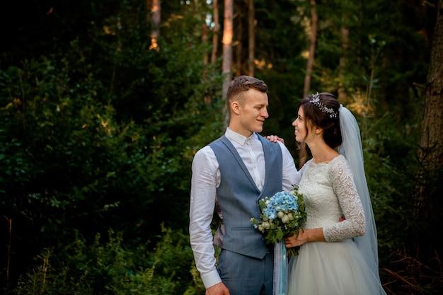 Beau couple de jeunes mariés marchant dans la forêt
