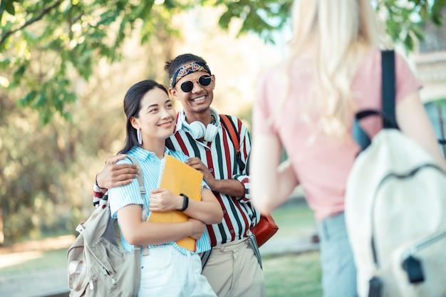 Beau couple joyeux d'étudiants rentrant ensemble à la maison après l'université