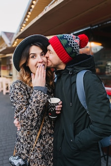 Beau couple joyeux se détendre, étreindre dans la rue à noël. véritables émotions d'amour, s'amuser, profiter de la convivialité, des rencontres, des relations amoureuses, du bonheur ensemble.