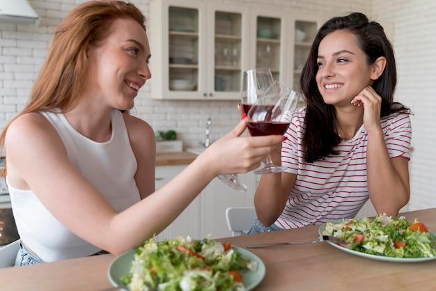 Beau couple de lesbiennes acclamant avec quelques verres de vin