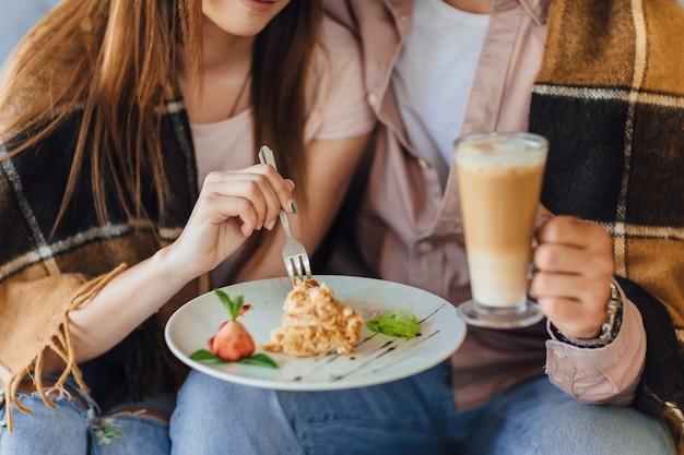 Beau couple mange un gâteau dans le café