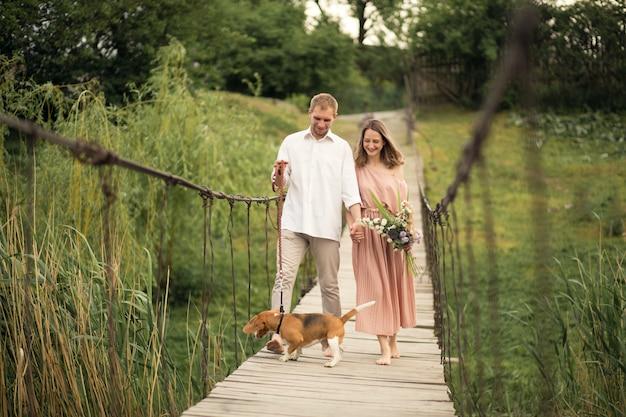 Beau couple marchant avec un chien sur le pont