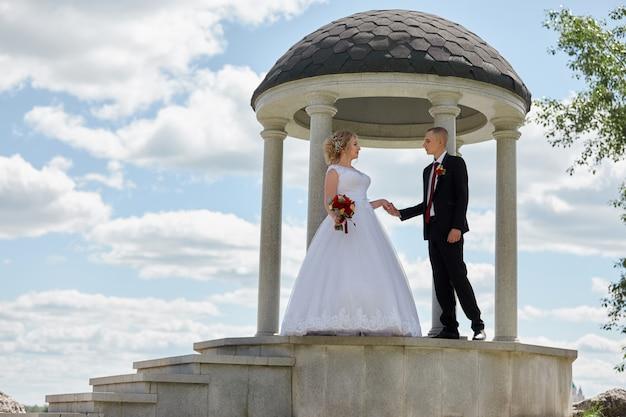 Un beau couple de mariage amoureux enregistre un mariage et se promène le long de la belle promenade.