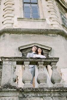Beau couple de mariage chinois debout sur le balcon d'un ancien château
