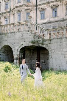 Beau couple de mariage chinois se promène près de l'ancien bâtiment, du vieux château à l'extérieur, du palais vintage en plein air.