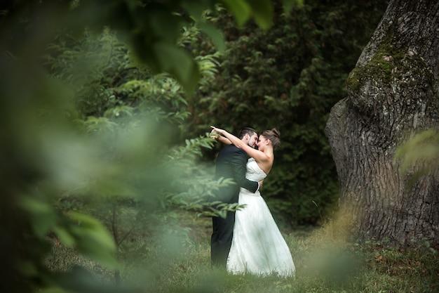 Beau couple de mariage dans les bras les uns des autres dans le parc