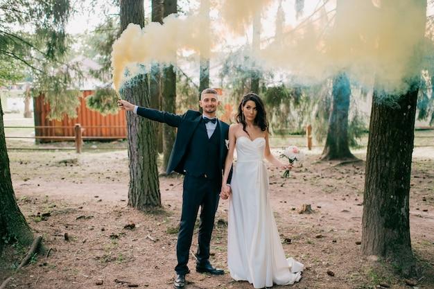 Beau couple de mariage debout ensemble à la nature et tenant une fumée colorée