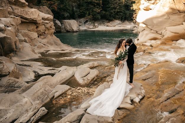 Beau couple de mariage étreint tendrement sur le fond d'une rivière de montagne, longue robe blanche de la mariée.