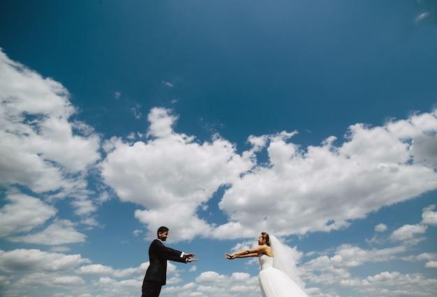 Beau couple de mariage sur fond de ciel bleu
