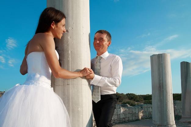 Beau couple de mariage mariée et le marié près de la colonne de la grèce dans la ville antique