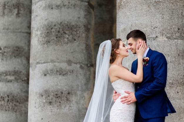 Beau couple de mariage pose devant un vieux château en ruine