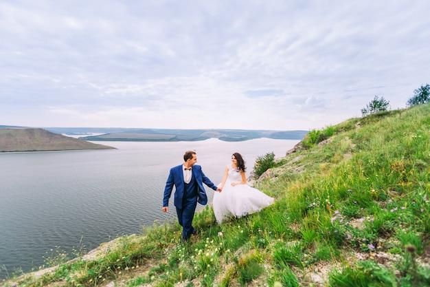 Beau couple de mariage sur une promenade romantique dans une merveilleuse baie.