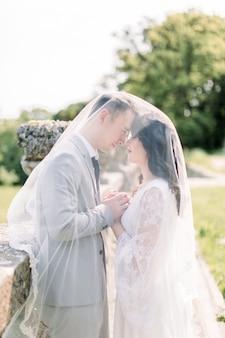 Beau couple de mariage romantique de jeunes mariés étreindre et main dans la main près de vieilles balustrades du château