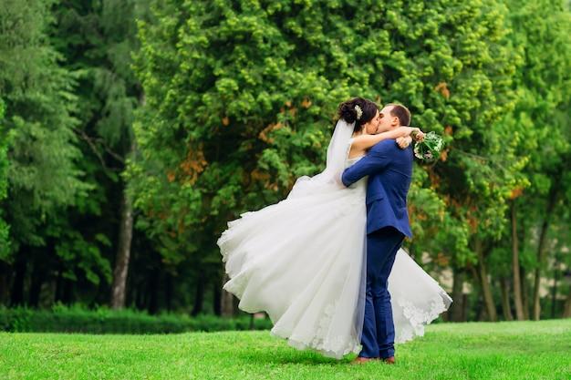 Beau couple de mariage tourne sur le pré s'embrassant. le marié et la mariée