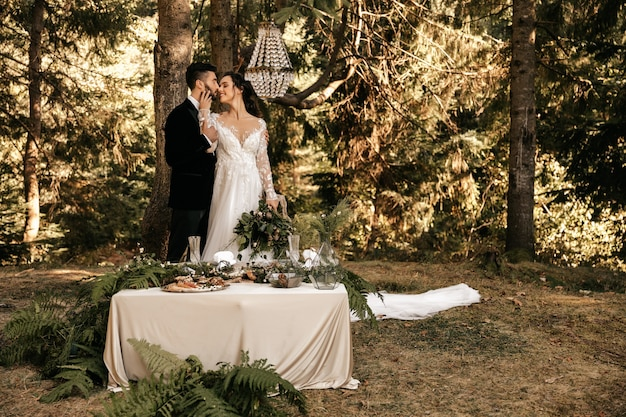 Beau couple de mariés étreignant sur le fond de la forêt.
