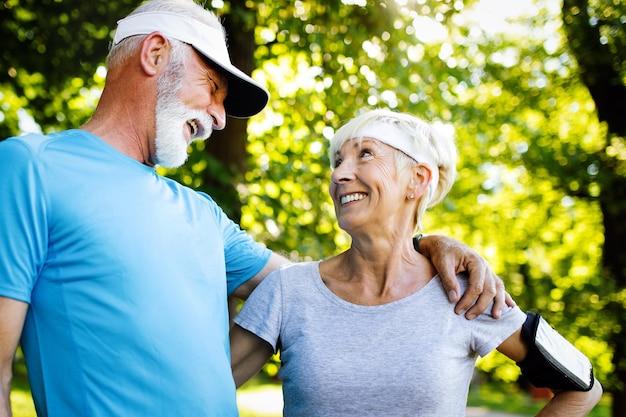 Beau couple mature jogging dans la nature vivant en bonne santé