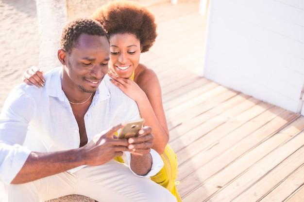 Beau couple de modèles africains de race noire utilisent le smartphone ensemble en souriant et en appréciant le contenu. connecté avec des amis ou en regardant les photos. amour, amis, couple, concept