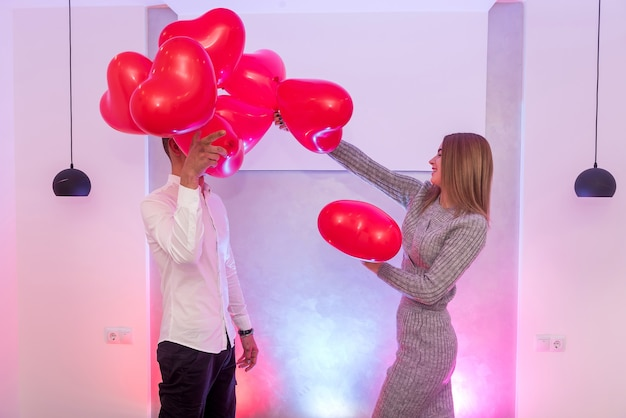 Beau couple avec des montgolfières rouges célébrant la saint-valentin qui pose en studio