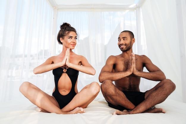 Beau couple multiracial médiant ensemble et assis en position du lotus sur le lit de plage