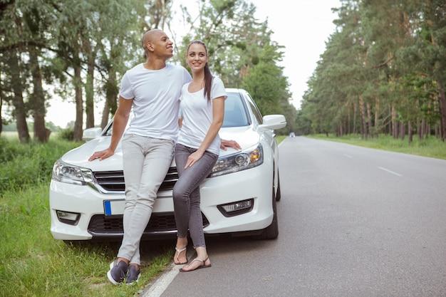 Beau couple multiracial profitant de voyager en voiture