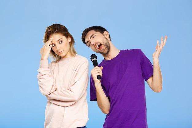 Beau couple sur mur bleu homme chantant dans la fille du microphone mécontent.