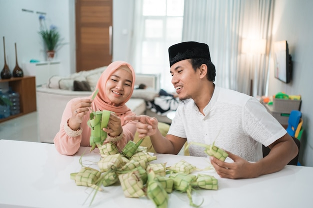Beau couple musulman asiatique faisant un gâteau de riz ketupat à la maison à l'aide de feuilles de palmier