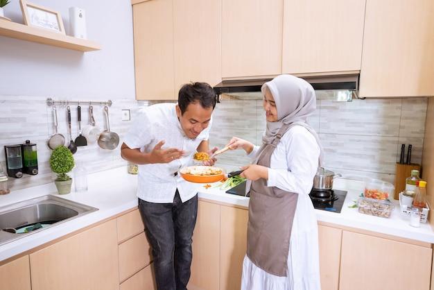 Beau couple musulman asiatique profiter d'un repas de cuisine ensemble dans la cuisine