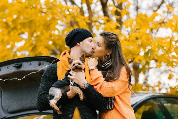 Beau couple passe du temps dans un parc d'automne avec leur ami chien. les amoureux s'embrassent