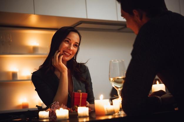 Beau couple passionné ayant un dîner romantique aux chandelles à la maison, boire du vin, femme obtenant une boîte-cadeau