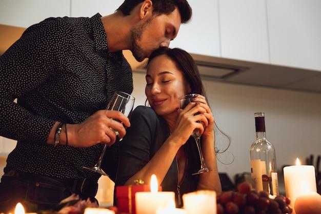 Beau couple passionné ayant un dîner romantique aux chandelles à la maison, s'embrasser