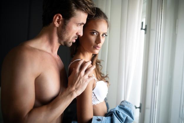 Beau couple passionné fait l'amour dans une chambre. portrait de passion, plaisir, sexe, relation.