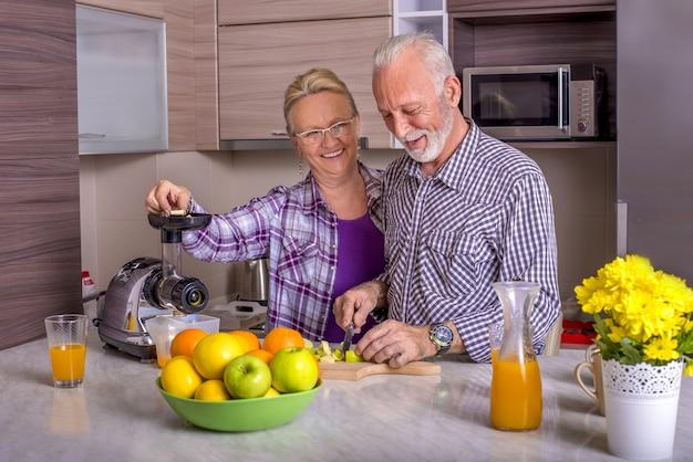 Beau couple de personnes âgées cuisiner dans la cuisine les uns avec les autres