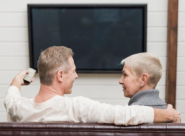 Beau couple de personnes âgées devant la télé