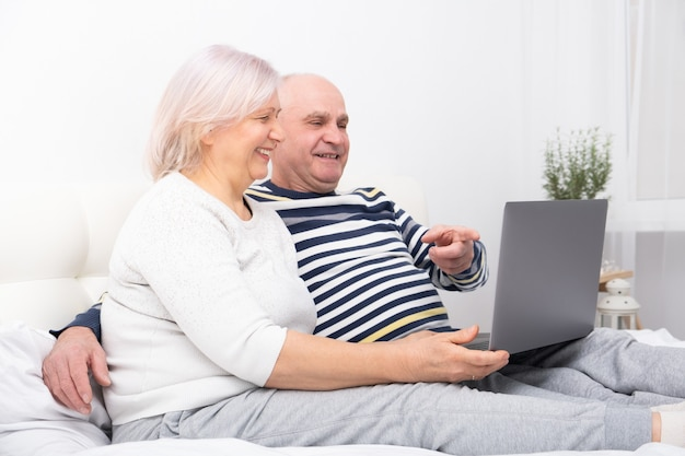 Beau couple de personnes âgées femme et homme assis dans son lit à l'aide d'un ordinateur portable à la maison