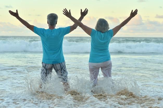 Un beau couple de personnes âgées heureux se repose dans un complexe tropical avec les mains en l'air