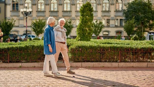 Beau couple de personnes âgées parlant de quelque chose en marchant dans le parc par une journée ensoleillée