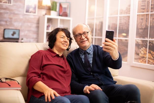 Beau couple de personnes âgées prenant un selfie assis sur le canapé du salon