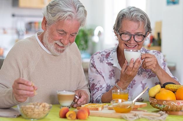 Beau couple de personnes âgées prenant son petit déjeuner à la maison. mode de vie à la retraite