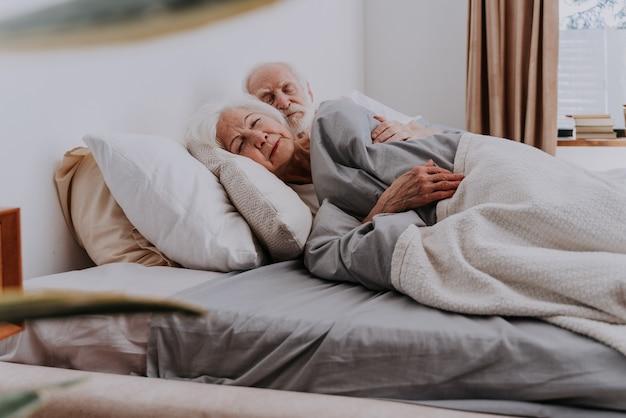 Beau couple de personnes âgées profitant du temps ensemble à la maison - personnes âgées dormant dans leur lit à la maison