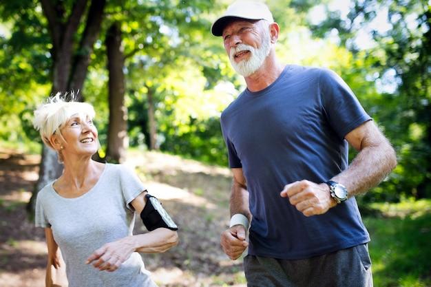 Beau couple de personnes âgées qui court dehors dans la forêt ensoleillée