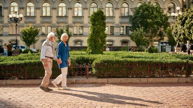 Beau couple de personnes âgées se tenant la main en marchant ensemble dans la rue