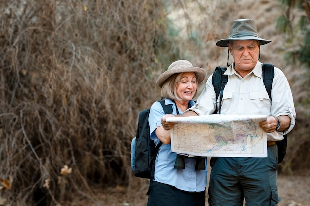 Beau couple de personnes âgées utilisant une carte pour rechercher la direction