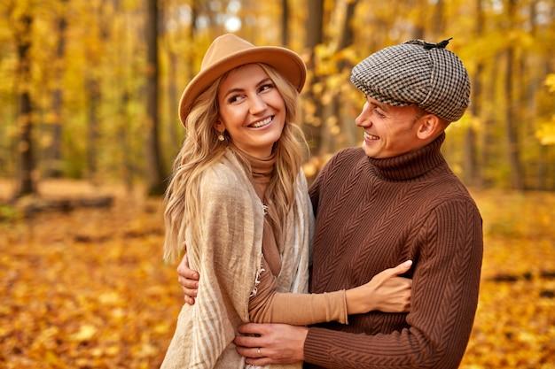 Beau couple posant dans la forêt d'automne, amoureux marchant dans le parc