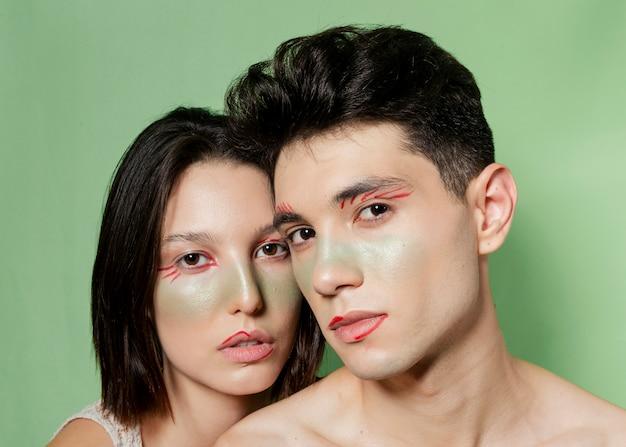 Beau couple posant avec des visages peints