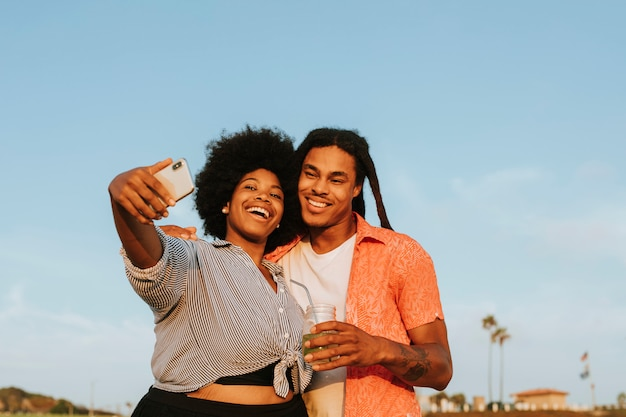 Beau couple prenant un selfie à la plage
