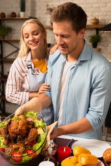 Beau couple prépare la dinde de thanksgiving