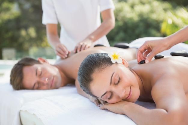 Beau couple profitant d'un massage aux pierres chaudes au bord de la piscine